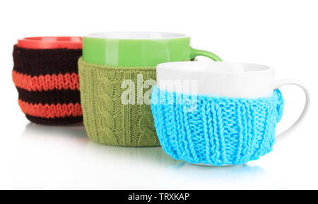 Cups with knitted things on it isolated on white - Stock Photo