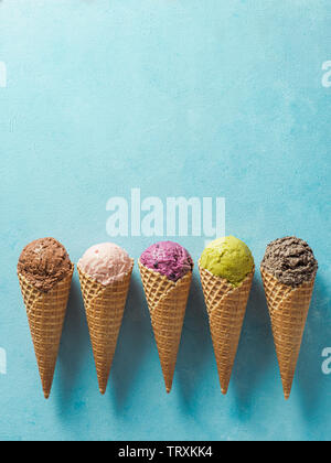 Various ice cream scoops in cones with copy space. Colorful ice cream in cones chocolate, strawberry, blueberry, pistachio or matcha, biscuits chocolate sandwich cookies on blue background. Top view - Stock Photo