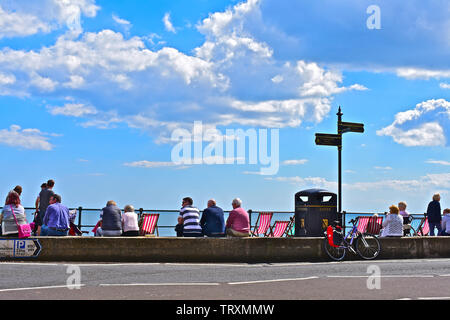 People sitting and relaxing on the sea wall in Sidmouth. Enjoying the sunshine overlooking the sea.Others walking along promenade.Striped deck chairs. - Stock Photo