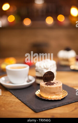Crumbles of chocholate on a tasty dessert with biscuit on top over a wooden table near a delicious coffee. Mini cake baked after traditional recipe. - Stock Photo