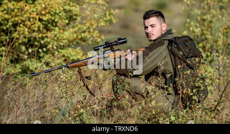 Hunting is brutal masculine hobby. Hunter hold rifle. Man wear camouflage clothes nature background. Hunting permit. Bearded serious hunter spend leisure hunting. Hunting equipment for professionals. - Stock Photo