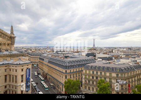 PARIS, FRANCE - JULY 22, 2017: Paris rooftops view and Eiffel Tower seen from Galeries Lafayette terrace in a cloudy day in France - Stock Photo