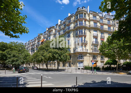 PARIS, FRANCE - JULY 21, 2017: Ancient luxury buildings facade and empty street with trees in a sunny summer day in Paris, France - Stock Photo