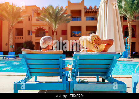 Senior couple relaxing by swimming pool lying on chaise-longues. People enjoying summer vacation.
