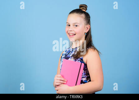 small girl with pink note book. school child with notepad. Smart and adorable. schoolgirl ready for lesson. school diaries for making note. love reading book. workbooks for writing. student read book. - Stock Photo