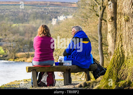 Couple of walkers, stopped for rest & picnic snack, sitting on bench with high scenic view to Barden Tower - Bolton Abbey Estate, Yorkshire Dales, UK. - Stock Photo