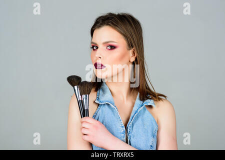 Looking good and feeling confident. Makeup dark lips. Attractive woman applying makeup brush. Professional makeup supplies. Makeup artist concept. Emphasize femininity. Girl apply powder eye shadows. - Stock Photo