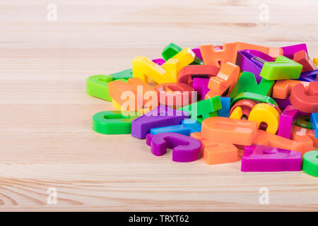 A pile of coloured magnetic letters over a school wooden table - Stock Photo