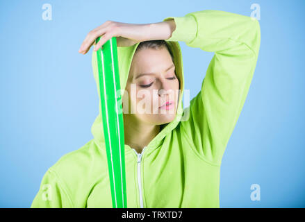 Girl hooded jacket hold baseball bat blue background. Woman in baseball sport. Baseball female player concept. Feeling power. She is dangerous. Woman play baseball game or going to beat someone. - Stock Photo