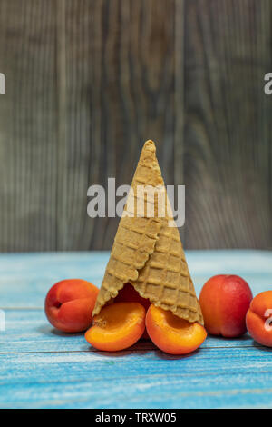 Fruit ice cream. Flat lay fresh apricotin a waffle cone on wooden background. Summer sweet menu concept. Homemade ice cream making - Stock Photo