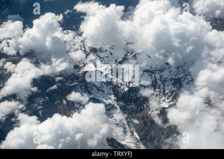 Flying at altitude over white cumulus clouds and the snow mountainous alps - Stock Photo