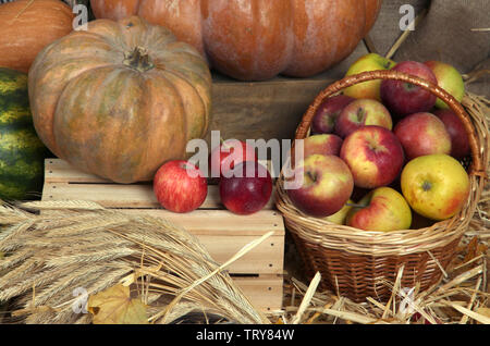 Pumpkins on crate and apples in basket on straw close up - Stock Photo