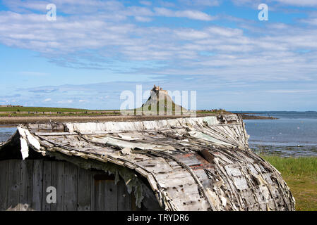 Old Upturned Fishing Boat Hulls Used as a Hut with Lindisfarne Castle on Holy Island Northumberland England United Kingdom UK - Stock Photo
