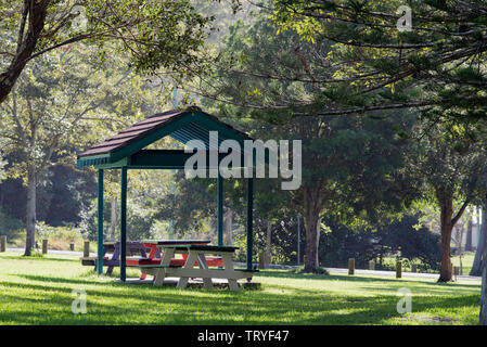 A terracotta tile roofed picnic eating area in a lush green park at Hallidays Point on the NSW mid north coast of Australia - Stock Photo