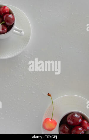 Cherries season. Top view of raw cherries in white cups and bowls - Stock Photo