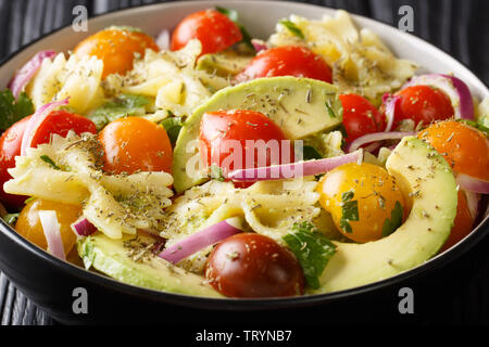 Farfalle pasta salad recipe with ripe avocado, onions and tomatoes closeup in a bowl on the table. horizontal - Stock Photo