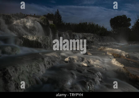 Night view of the famous free spa of the mill in Saturnia in Tuscany, Italy. A series of natural pools of hot water where people relax - Stock Photo