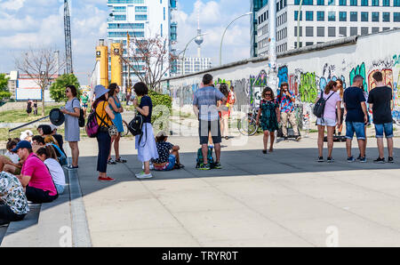 BERLIN, GERMANY - July 27, 2018: Graffiti art on original section of Berlin Wall at East Side Gallery in Friedrichshain. - Stock Photo