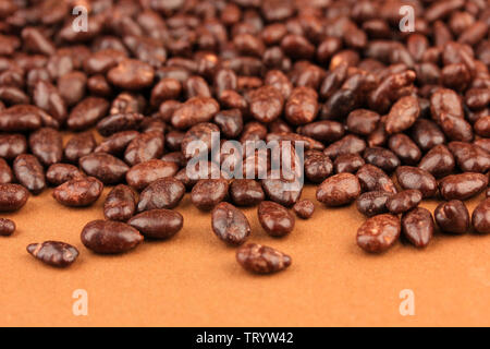 Sunflower grains in chocolate, on brown background - Stock Photo