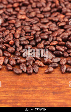 Sunflower grains in chocolate, on brown  wooden background - Stock Photo