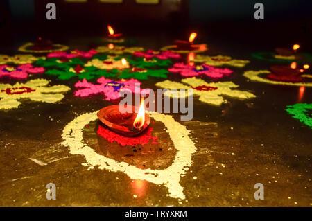 Diya Oil lamp in Rangoli decoration in Diwali festival. Concept of removing darkness. - Stock Photo