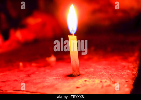 A christmas candle spreading light on black background in Diwali festival, a traditional celebration of India. - Stock Photo