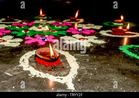 Happy Diwali. Diya Oil Lamps in DIPAWALI celebration decorated over Handmade Rangoli. - Stock Photo