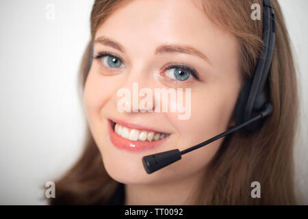 Happy smiling young caucasian woman with headset phone in a call center or office, close up - Stock Photo
