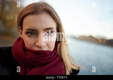 Portrait of a beautiful young white woman wearing a red scarf to keep warm in the cold of day - Stock Photo
