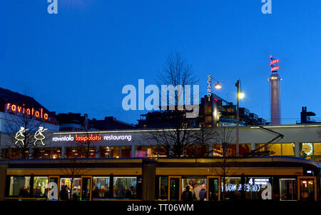 HELSINKI, FINLAND - 6 APRIL 2019: A tram car passes the neon-lit Ravintola restaurant in the Lasipalatsi complex, now including  Amos Rex art gallery. - Stock Photo