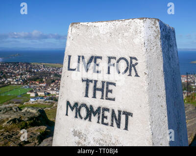 'Live for the moment' message on the triangulation pillar on the top of North Berwick Law, East Lothian, Scotland, UK. - Stock Photo