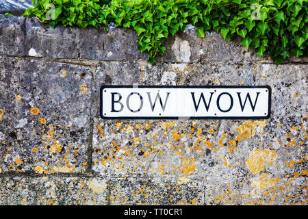 Unusual name sign of a small lane known as the Bow Wow in the Cotswold village of South Cerney in Gloucestershire. - Stock Photo
