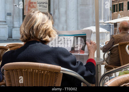 Italian Woman reading newspaper story about Theresa May, on the day after Theresa May, British Prime Minister announces that she will step down as Pri - Stock Photo