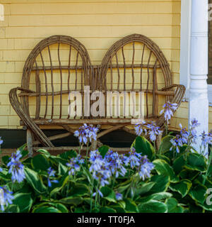Old fashioned loveseat made of twigs. - Stock Photo