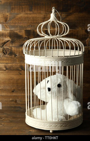 Toy rabbit in decorative cage  on wooden background - Stock Photo