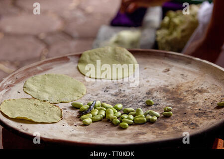 cooking tortillas on a mexican three stone stove fired by wood and broad beans, rural scene - Stock Photo