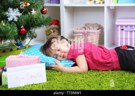 Little girl sleeping near Christmas tree in room