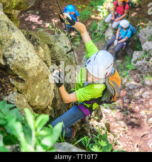 Hiking and climbing on a forestry and rocky trail with via ferrata passages - Stock Photo