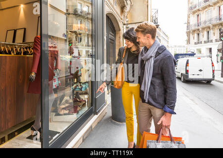 Happy, stylish couple looking through shop store window shopping in Paris, France - Stock Photo