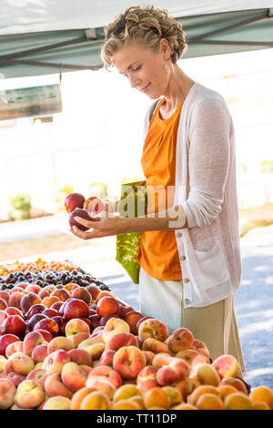 Beautiful, happy, healthy middle aged mature woman shopping for fresh organic produce fruit at farmers market - Stock Photo