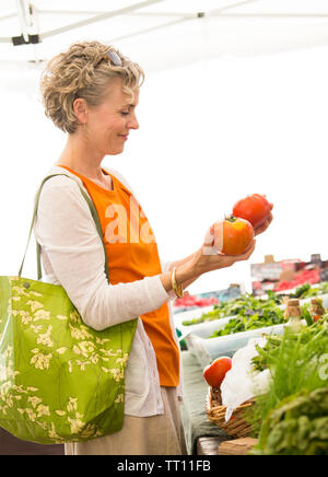 Beautiful, happy, healthy middle aged mature woman shopping for fresh organic produce tomatoes at farmers market - Stock Photo