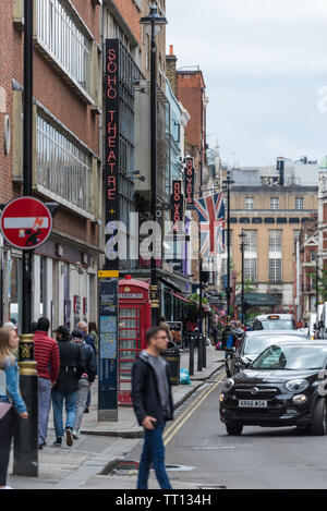 General view along Dean Street with neon signs for Quo Vadis restaurant and Soho Theatre Bar, Soho, London. Road traffic and people on the street - Stock Photo