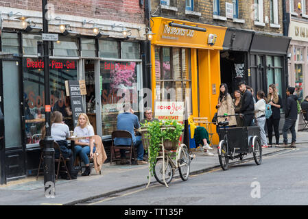 People seated outside Soho Joe restaurant and a group of young people queue on the street for entry to The Breakfast Club, D'Arblay Street, Sohod - Stock Photo
