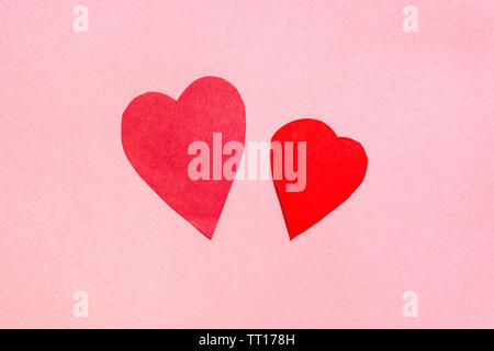 two hearts cut from red paper on pink paper background - Stock Photo