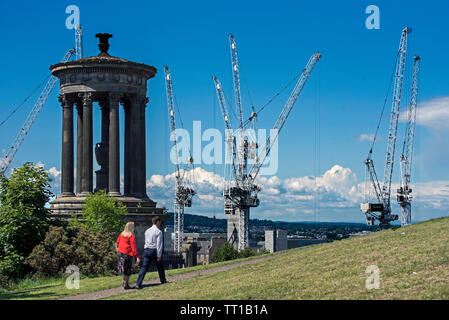 A couple walk by the Dugald Stewart Monument on Calton Hill, Edinburgh. In the background are cranes working on the St James Project. - Stock Photo