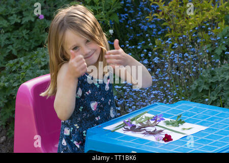 three year old girl giving thumbs up sitting at a small table, proud of a picture made from flowers and leaves stuck on paper, nature art craft - Stock Photo