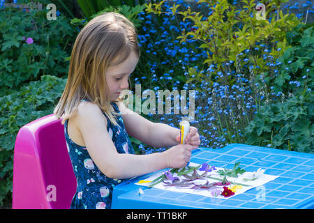 three year old girl in a dress sitting at a small table in garden, making a picture made from flowers and leaves stuck on paper, nature art craft - Stock Photo