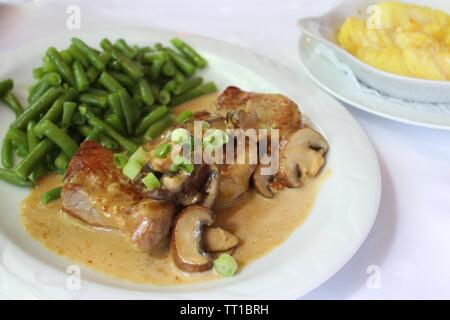 Medaillons of pork with potato gratin, green beans, mushrooms and cream sauce on white plate - Stock Photo