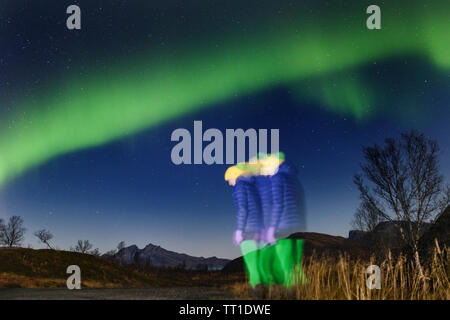 Woman wearing colorful clothing stands under the green aurora in Tromso, Arctic Norway - Stock Photo