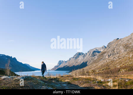 Woman walks alone in a Norwegian fjord during autumn with snowy frost on the ground